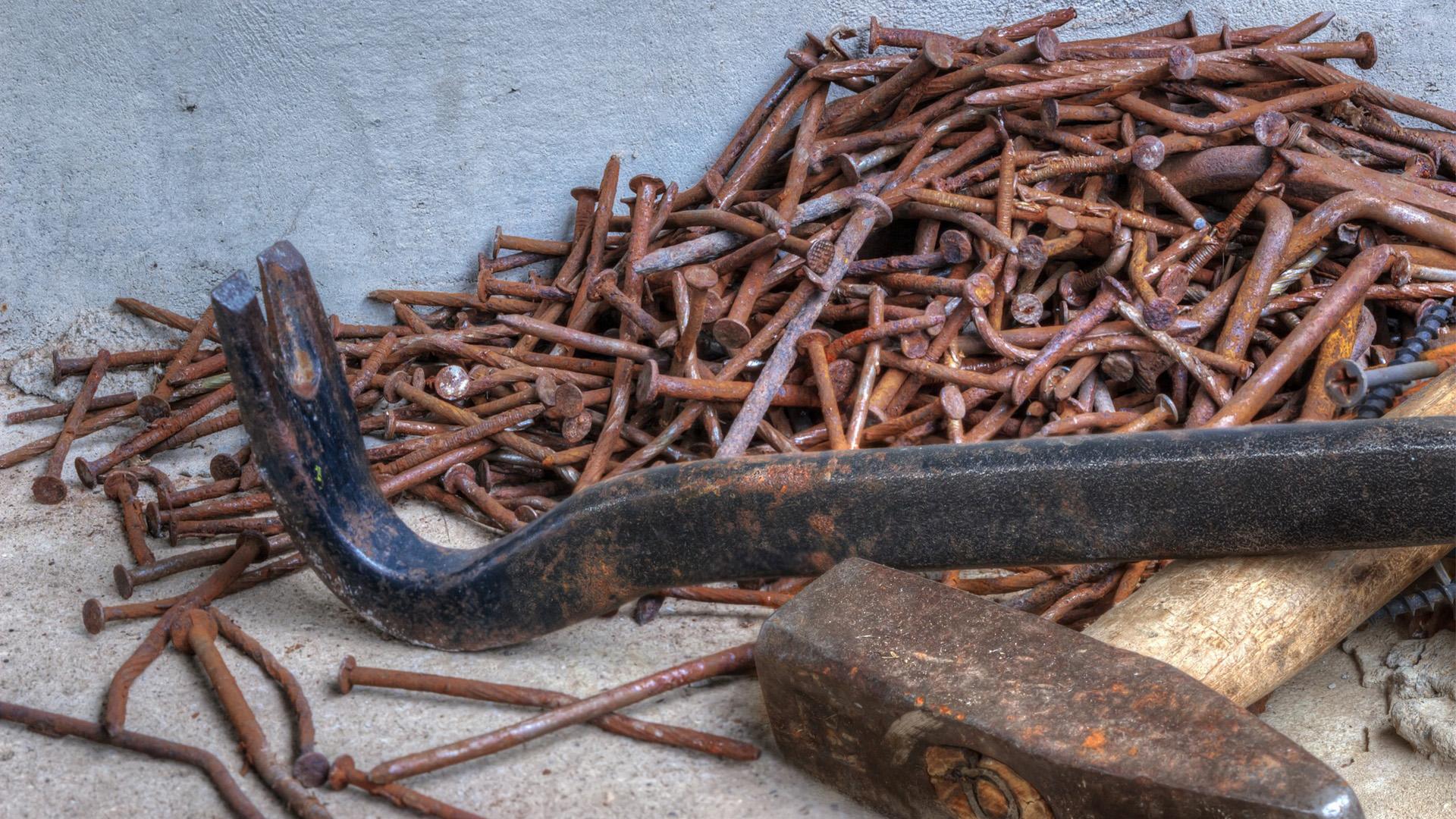 Spijkers, koevoet en hamer ter illustratie van losmaakbaarheid